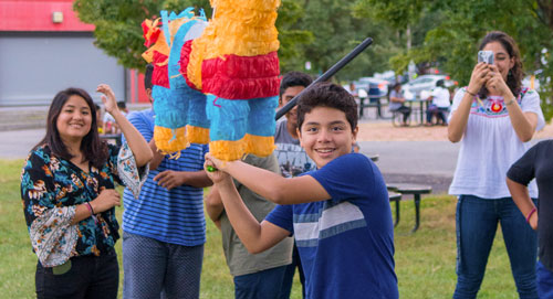 Teen smiling and hitting piñata